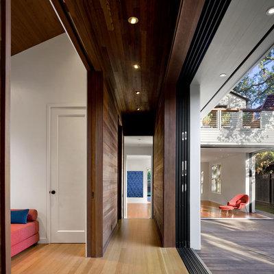 Hallway - contemporary medium tone wood floor hallway idea in San Francisco with white walls
