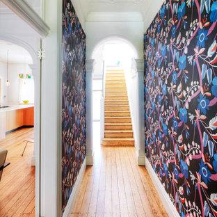 Foto på en mellanstor funkis hall, med flerfärgade väggar och mellanmörkt trägolv