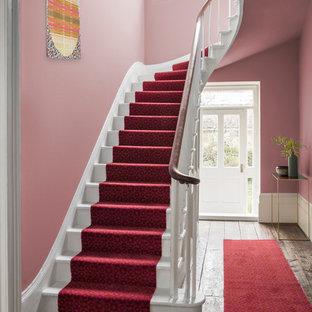 Bild på en funkis hall, med rosa väggar och heltäckningsmatta