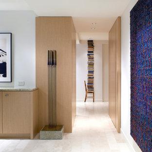 Exemple d'un couloir tendance avec un mur blanc, un sol en calcaire, un sol beige et du lambris.