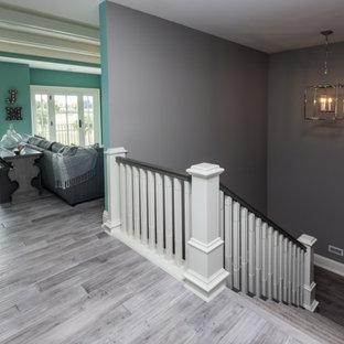 Exemple d'un couloir chic de taille moyenne avec un mur gris, un sol en bois peint et un sol gris.