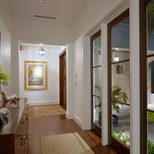 Inspiration för en mellanstor tropisk hall, med vita väggar, mellanmörkt trägolv och brunt golv
