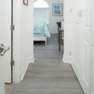 Inspiration for a mid-sized beach style hallway in Orlando with vinyl floors, grey floor and white walls.