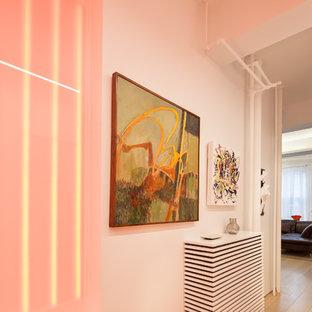 Cette photo montre un couloir tendance de taille moyenne avec un mur blanc, un sol en bois clair et un sol beige.