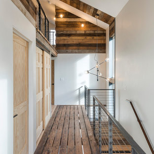 Example of an urban dark wood floor and brown floor hallway design in Providence with white walls