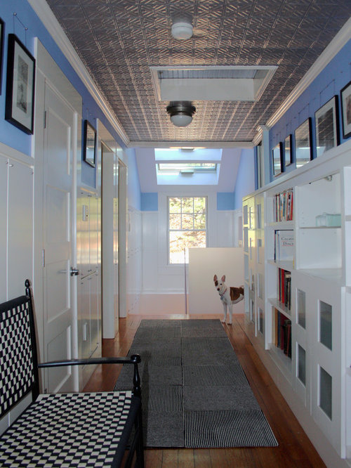 inspiration for a timeless medium tone wood floor hallway remodel in boston with white walls