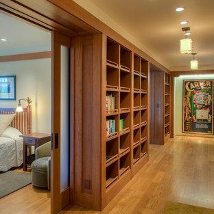 Cette image montre un couloir craftsman avec un mur beige et un sol en bois brun.