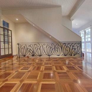 На фото: большой коридор в классическом стиле с белыми стенами, паркетным полом среднего тона, деревянным потолком и деревянными стенами