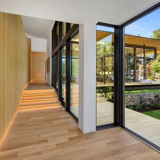 Idée de décoration pour un couloir design avec un sol en bois clair et un sol beige.