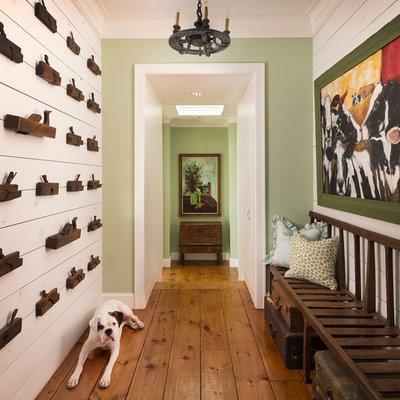 Cottage medium tone wood floor hallway photo in Dallas with green walls