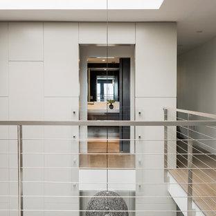 Exemple d'un couloir moderne avec un mur blanc, un plafond voûté et du lambris.