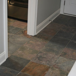 This is an example of a small arts and crafts hallway in Grand Rapids with grey walls and slate floors.