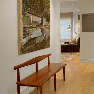 Exemple d'un couloir tendance de taille moyenne avec un sol en bambou et un mur blanc.