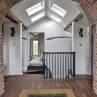 Свежая идея для дизайна: коридор среднего размера в скандинавском стиле с белыми стенами, темным паркетным полом, коричневым полом, балками на потолке и кирпичными стенами - отличное фото интерьера