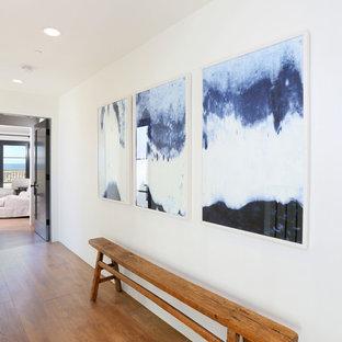 Inspiration pour un couloir marin avec un mur blanc et un sol en bois brun.