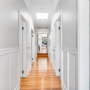Aménagement d'un couloir classique avec un sol en bois clair et boiseries.