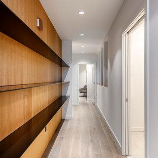 Cette photo montre un couloir tendance de taille moyenne avec un mur blanc, un sol en bois clair et du lambris.