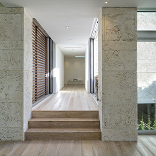 Mid-sized beach style hallway in Miami with beige walls, bamboo floors and beige floor.