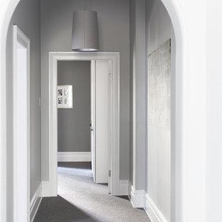 Aménagement d'un grand couloir victorien avec un mur gris, moquette et un sol gris.