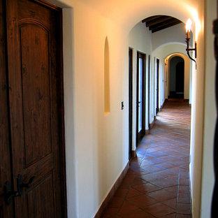 Стильный дизайн: коридор среднего размера в средиземноморском стиле с белыми стенами, полом из терракотовой плитки и красным полом - последний тренд