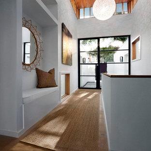 На фото: большой коридор в стиле модернизм с белыми стенами и паркетным полом среднего тона