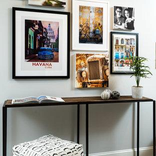 Idées déco pour un petit couloir moderne avec un mur gris, un sol en bois clair et un sol jaune.