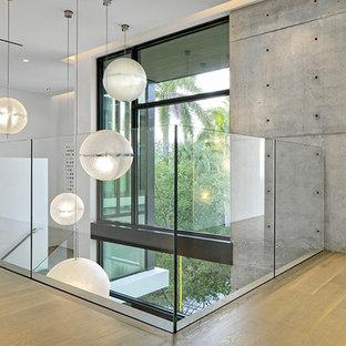 Cette image montre un très grand couloir minimaliste avec un mur blanc, un sol en bambou et un sol beige.