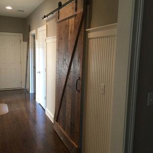 Idée de décoration pour un grand couloir chalet avec un mur marron et un sol en bois foncé.