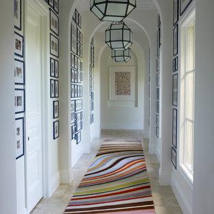 Exemple d'un couloir chic avec un mur blanc et un sol en travertin.
