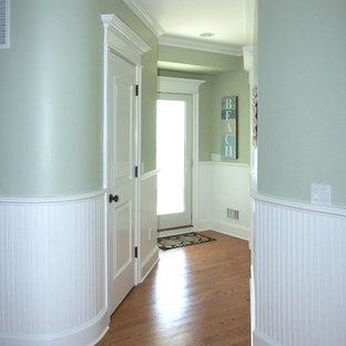This is an example of a large beach style hallway in New York with green walls and light hardwood floors.