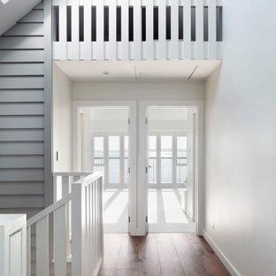 オークランドの中くらいのコンテンポラリースタイルのおしゃれな廊下 (白い壁、無垢フローリング、茶色い床、三角天井) の写真