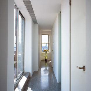 Modern inredning av en hall, med vita väggar, terrazzogolv och grått golv