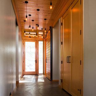 Immagine di un ingresso o corridoio stile rurale di medie dimensioni con pareti bianche, pavimento in cemento e pavimento grigio
