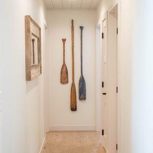 Inredning av en maritim mellanstor hall, med vita väggar, ljust trägolv och beiget golv