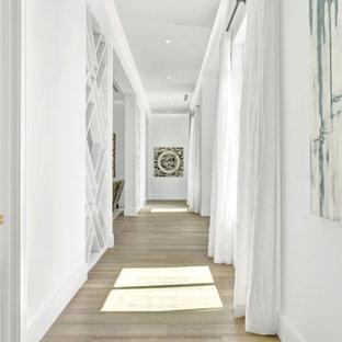 Idéer för en mycket stor modern hall, med vita väggar, ljust trägolv och beiget golv