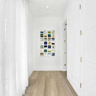 Idées déco pour un très grand couloir contemporain avec un mur blanc, un sol en bois clair, un sol beige et un plafond à caissons.