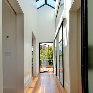 Réalisation d'un couloir design avec un mur blanc, un sol en bois brun et un sol jaune.