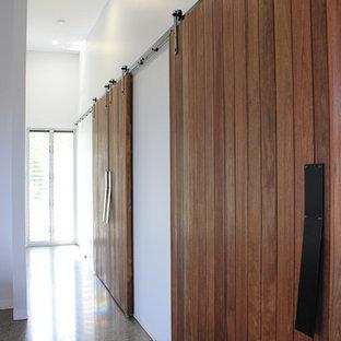 他の地域の小さいコンテンポラリースタイルのおしゃれな廊下 (白い壁、コンクリートの床、マルチカラーの床) の写真