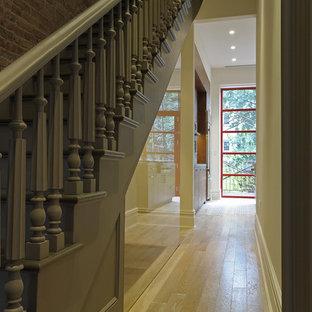 Idée de décoration pour un couloir tradition avec un mur beige, un sol en bois clair et un sol jaune.