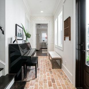 Diseño de recibidores y pasillos tradicionales con paredes blancas, suelo de ladrillo y suelo rojo