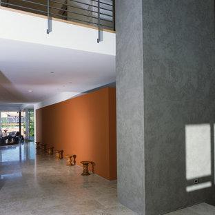 Idée de décoration pour un couloir minimaliste avec un mur orange et un sol gris.