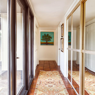 Mid-sized midcentury hallway in Houston with white walls, terra-cotta floors and brown floor.