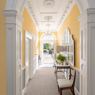 Ispirazione per un ingresso o corridoio classico di medie dimensioni con pareti gialle e moquette