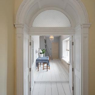 Inredning av en klassisk stor hall, med gula väggar, målat trägolv och vitt golv