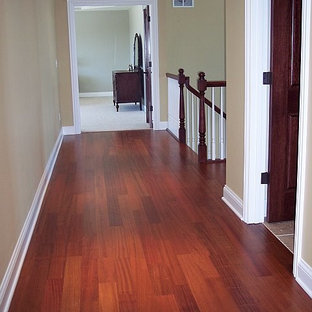 Inspiration for an expansive traditional hallway in Milwaukee with beige walls and dark hardwood floors.