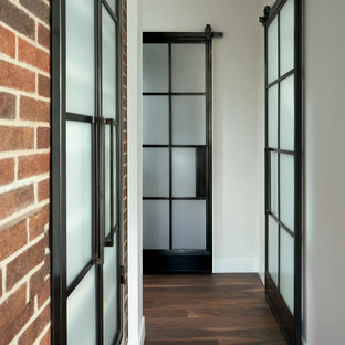 Photo of a modern hallway in Denver with white walls and dark hardwood floors.