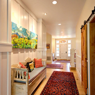 Inspiration for a mid-sized country medium tone wood floor and brown floor hallway remodel in Other with white walls