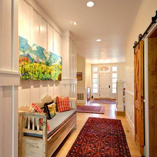 Cette photo montre un couloir nature de taille moyenne avec un mur blanc, un sol en bois brun et un sol marron.