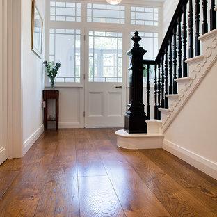 Cette photo montre un couloir moderne de taille moyenne avec un mur blanc et un sol en bois foncé.