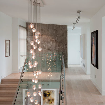 Example of a trendy light wood floor hallway design in Vancouver with white walls